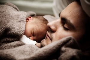 Dad sleeping with infant.