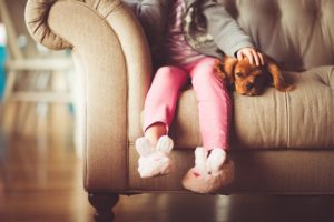 Girl on couch petting dog.