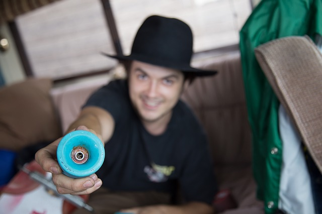 Man showing close up of blue skateboard wheel.