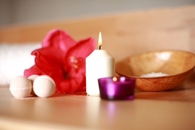 Candle burning with flower and bath balls.