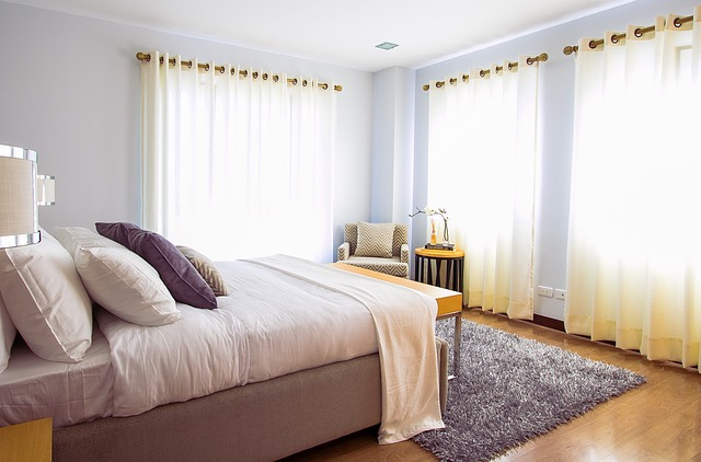 Comfortable bed in a sunny bedroom.