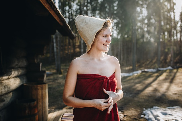 Woman enjoying the outdoors wearing a sauna cap and towel.
