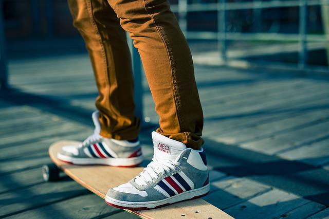 Standing on a skateboard.