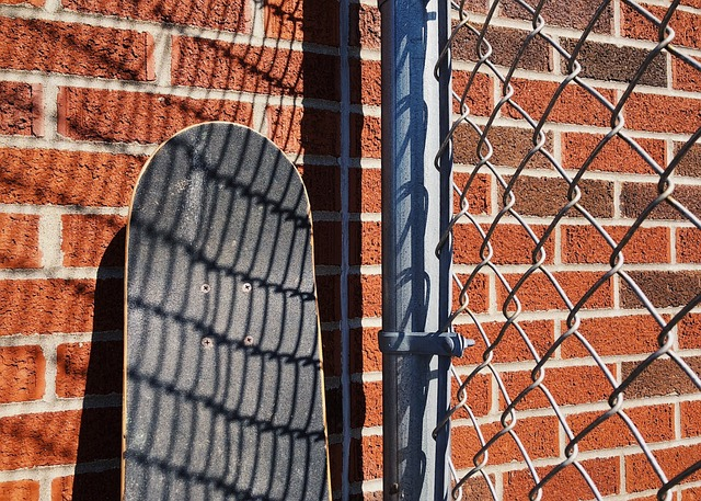 Skateboard propped on brick wall.