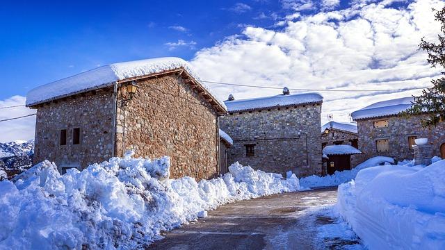 Snowy plowed road in village.