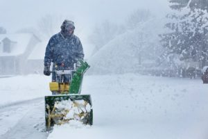 Man using snow blower while snowing.