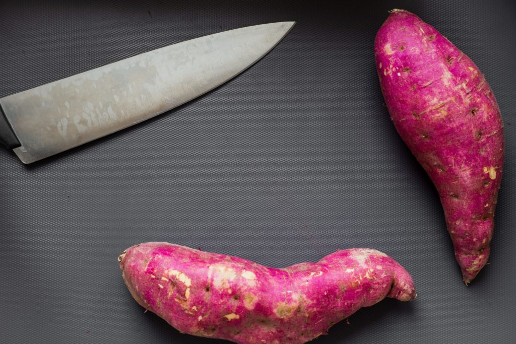 Red sweet potatoes and knife.