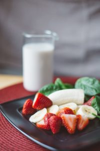 Strawberry and bananas on plate.